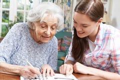 少年有纵横填字游戏的孙女帮助的祖母 免版税库存图片