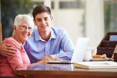 少年有膝上型计算机的孙子帮助的祖母 免版税图库摄影