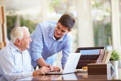 少年有膝上型计算机的孙子帮助的祖父 免版税库存图片