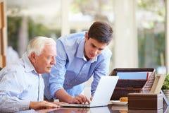 少年有膝上型计算机的孙子帮助的祖父 库存照片