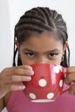 少年杯子饮用的女孩大一点的te 免版税库存图片