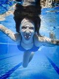 少年游泳水下在池 免版税库存照片