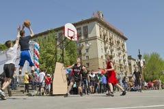 少年演奏在露天沥青地面的streetball 免版税库存照片