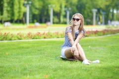 少年生活方式概念 摆在Longboard的逗人喜爱和正面白种人白肤金发的少年女孩画象在绿色夏天公园 库存图片