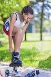少年生活方式概念 非裔美国人的十几岁的女孩在公园投入溜冰鞋户外 免版税库存照片