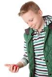 少年男孩举行一个红色复活节彩蛋在他的手上 免版税库存照片