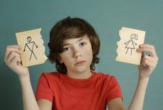 少年男孩举行在两个被撕毁的纸片断的妈妈和爸爸图画 库存图片
