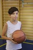 少年男孩健身房的蓝球运动员与球 库存图片