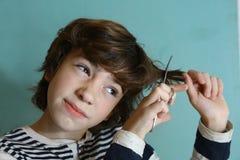 少年男孩剪了他的有剪刀的头发 免版税库存图片