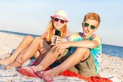 少年(男孩和女孩)使用巧妙的电话和听的音乐 库存照片