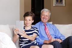 少年男孩和他的祖父 免版税库存照片