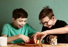 少年男生烹调吃热狗 图库摄影