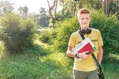 少年的男小学生在城市公园站立 免版税库存图片