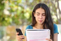 少年看斜向一边手机的学生女孩,当学习时 库存图片