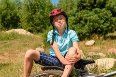 少年从自行车下落了和受了损伤 免版税库存图片