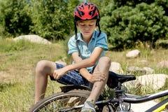 少年从自行车下落了和受了损伤 免版税图库摄影