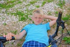 少年从自行车下落了和受了损伤 库存照片