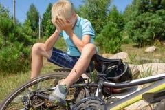 少年从自行车下落了和受了损伤 库存图片