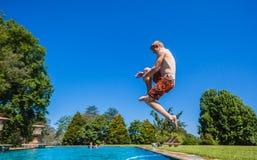 少年跳跃的游泳池 库存图片
