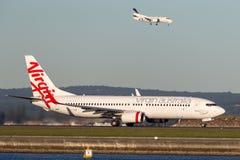 维尔京澳大利亚航空公司在悉尼机场的波音737-800航空器和雷克斯登陆的绅宝340后边 免版税库存图片