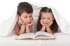 柴尔兹在床上读了书在毯子下 库存图片