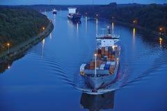 贝尔多尔夫-在基尔运河的集装箱船在晚上 库存图片