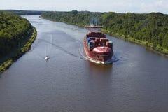 贝尔多尔夫-在基尔运河的集装箱船 免版税库存照片