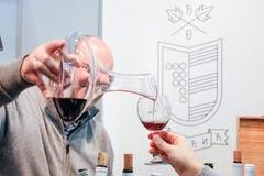 贝尔格莱德,塞尔维亚- 2017年2月25日:涌入品酒的一块玻璃的红葡萄酒在公平2017年贝尔格莱德的旅游业期间 库存图片