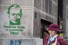 贝尔格莱德,塞尔维亚- 2014年11月7日:通过一张赞成俄国街道画弗拉基米尔・普京的老妇人在贝尔格莱德观看您 免版税库存图片