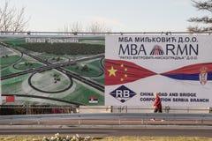 贝尔格莱德,塞尔维亚- 2014年12月25日:通过广告牌的妇女促进中国投资在塞尔维亚在新打开的P附近 免版税库存照片