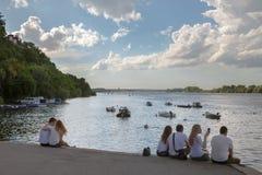 贝尔格莱德,塞尔维亚- 2017年5月13日:青年人坐泽蒙奎伊Zemunski Kej在日落,在多瑙河的观看的日落 免版税库存图片