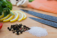 绍尔特在砧板的胡椒用蕃茄、荷兰芹和刀子和未加工的salamon 库存图片