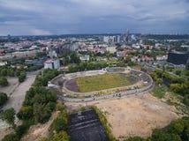 维尔纽斯,立陶宛- 2016年7月11日:飞行在维尔纽斯和Zalgiris体育场在背景中 蓝色多云天空 图库摄影