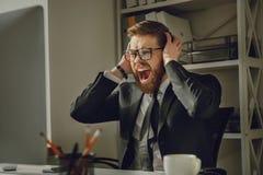 尖叫一个沮丧的有胡子的商人的画象在镜片的 免版税库存图片