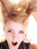 尖叫和拉扯杂乱头发的恼怒的愤怒的妇女 免版税库存图片