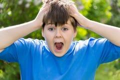 尖叫和握在他的头后的青少年的男孩手 免版税图库摄影
