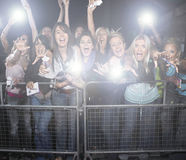 尖叫和欢呼在音乐会的年轻女性爱好者人群  免版税库存照片