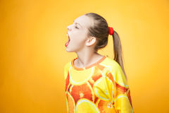 尖叫女孩佩带的桔子打印的运动衫 库存图片