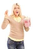 尖叫害怕的白肤金发的妇女拿着玉米花配件箱和 免版税图库摄影