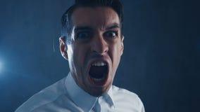 尖叫恼怒的商人的特写镜头,显示恐惧、愤怒和失望 股票录像