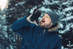 尖叫有胡子的人旅客林务员猎人画象在冬天森林里 免版税库存图片
