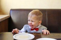 尖叫生气和哭泣的小男孩,当坐在桌上时 免版税库存照片