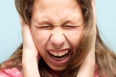 尖叫的女孩紧紧关闭了眼睛儿童盖子耳朵 免版税图库摄影