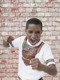尖叫蓬松卷发的男孩,握紧拳头,十岁 免版税库存图片