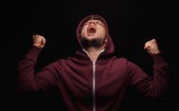 尖叫,在黑背景的病的男性 有冠乌鸦的被注重的学生 遭受在痛苦中的人 愤怒发布概念 免版税库存照片
