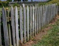 尖桩篱栅饱经风雨与里里外外绿色叶子 库存图片