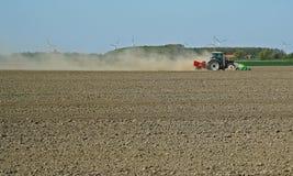 尘土云彩在一台耕的拖拉机后的在春天期间在西兰省 库存图片