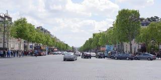 尚萨斯-爱丽舍宫 在车行道移动的汽车上,步行者在边 免版税库存照片