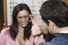 尝试不同的眼睛玻璃的妇女劝告一个人 免版税库存图片