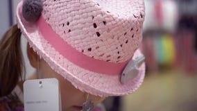 尝试在一个新的桃红色帽子和使用智能手机的一个小女孩 股票视频